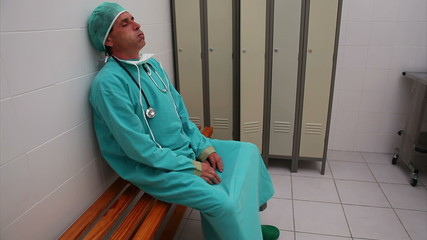 Tired surgeon sitting on a bench