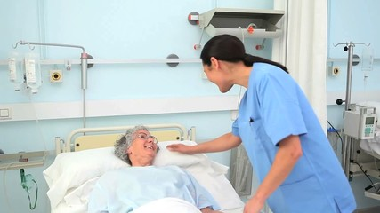 Nurse smiling to a patient while holding her hand