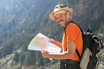 Tourist hiker with map in mountains