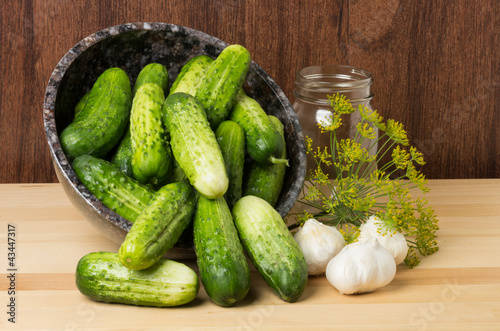 Bowl of pickles with jar and garlic