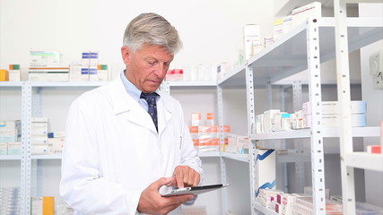 Pharmacist standing behind a hospital counter