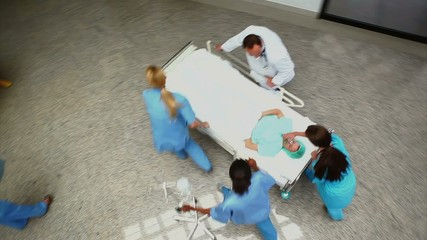 High angle view of a medical team wheeling a patient on a bed