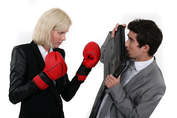 Woman with boxing gloves attacking colleague