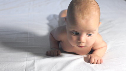Baby boy tries to keep his head and crawl on blanket