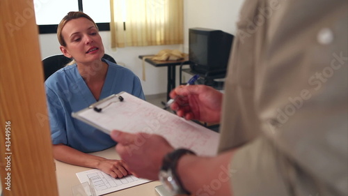 Nurse looking at files at a reception desk