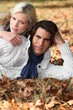 Couple laying in fallen leaves