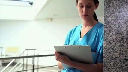 Serious nurse writing on a clipboard