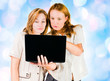 Two young businesswomen working on laptop.