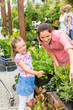 Mother daughter choosing flowers in garden shop
