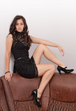 Attractive brunette sitting on sofa in a sexy position poster