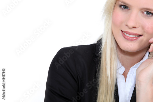 Studio closeup of young beautiful blonde in a suit