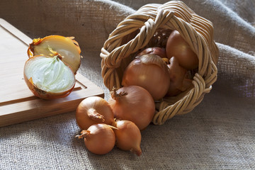 Loose onions scattered from wicker basket
