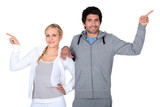 happy couple training together pointing at different directions