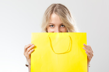 blonde woman behind yellow shopping bag