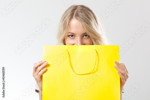 blonde woman behind yellow shopping bag