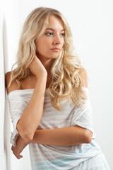 beautiful blonde woman near white wall