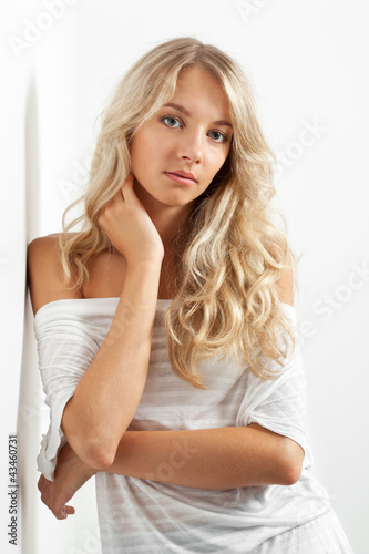beautiful blonde woman near white wall