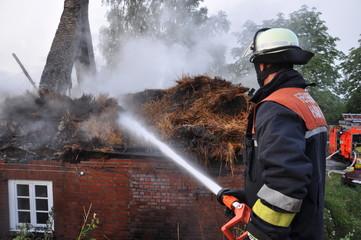 Feuerwehrmann löscht Reetdach