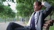 Happy businessman relaxing on bench in the park, tracking shot