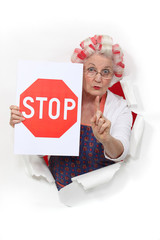 Granny holding a stop sign and with her hair in rollers