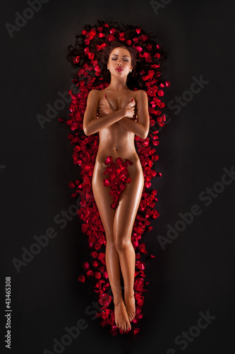 Beautiful woman against petals of red roses on black