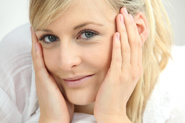 Relaxed smiling woman with her head in her hands