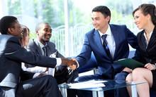 Dwóch biznesmenów wstrząsając ręce mężczyzna ze swoim zespołem w biurze