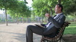 Young happy businessman relaxing on bench in the park
