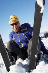 Male Skier Sitting In Snow With After Fall