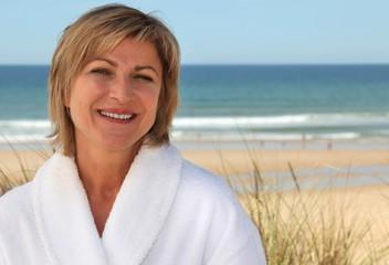 Woman with a bathrobe on the beach