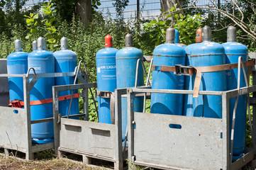 Blaue Gasflaschen im Transport-Container