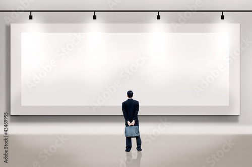 Businessman looking at an empty billboard