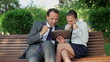 Successful business couple with tablet computer in the park,