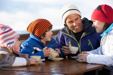 Family Enjoying Hot Drink In Café At Ski Resort