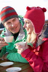 Couple Enjoying Hot Drink In Café At Ski Resort
