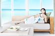 Woman having tea in beach apartment