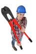 Happy female builder with bolt-cutters