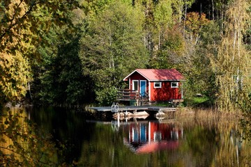 Typical Swedish red little cottage at a lake