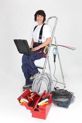 Woman electrician sitting on a ladder with laptop