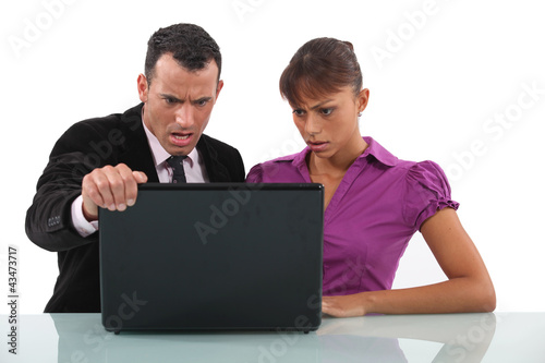 businessman and secretary getting angry over laptop