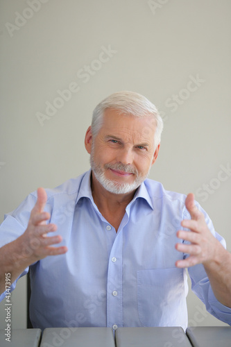 Elderly man holding up his hands