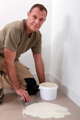 Handyman spreading adhesive over an old tiled floor