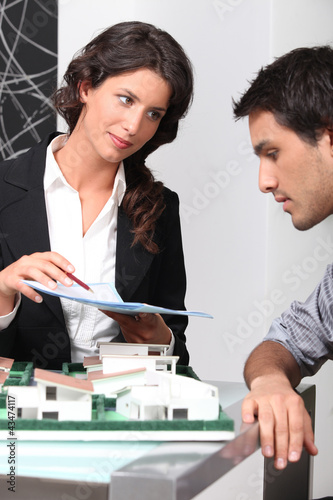 Estate agent and client discussing contracts