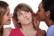 Doubtful woman surrounded by gossipers