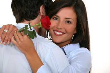 woman hugging boyfriend with red rose in hand