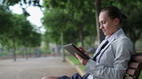 Businesswoman using tablet computer in the park, tracking shot