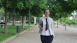 Young smiling businesswoman walking in the park, slow motion