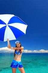 水辺でパラソルを持つ笑顔の女性