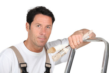 A painter and decorator leaning against a ladder