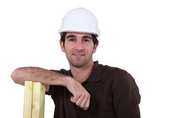 Man leaning on planks of wood